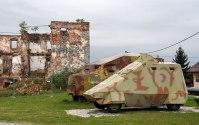"""Die im Krieg zerschossene Ruine ist teil des Militärmuseums in Turanj. Auf Kroatischer Seite gab es zu Beginn des Krieges kaum Militärmaterial. Autos und Traktoren wurden provisorisch mit Platten """"bepanzert""""."""